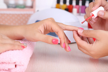 Young woman is getting manicure in beauty salon, close-up