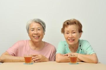 お茶を飲んで休憩している高齢者のアジア人二人組