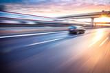 Fototapety Car driving on freeway at sunset, motion blur