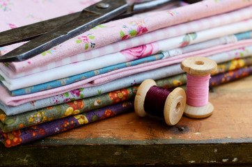 Set of fabrics, wooden thread spools and tailor scissors