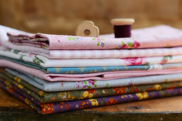 Stack of floral pattern textile and wooden spools