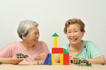 積み木と家の模型で遊んでいる二人のアジア人高齢者