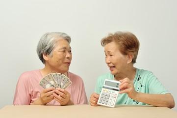お金の計算をしているシニアの女性二人組