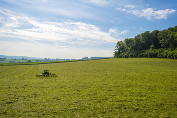 Tractor mowing in a meadow in summer
