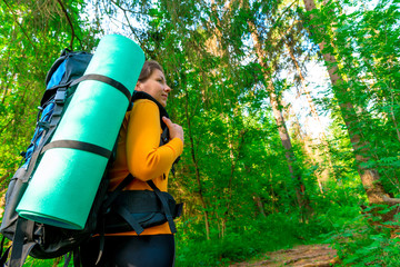tourist with a backpack in the woods in search of the road
