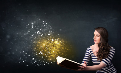 Young lady reading a magical book