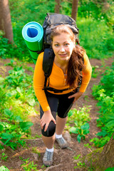 woman with a backpack up the hill in the woods