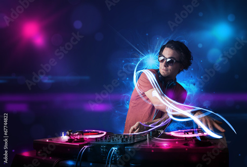 Disc jockey playing music with electro light effects and lights - 67744822