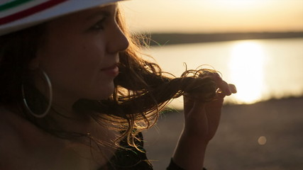 Beautiful young woman at sunset. Close-up, shallow DOF.