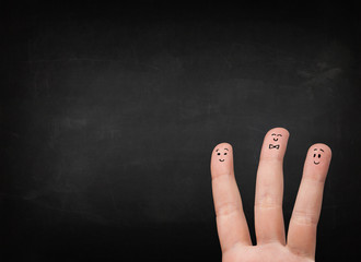Happy smiley fingers looking at empty black chalboard