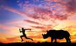 Man running away from Rhino