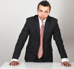 Young man standing near desk, isolated on white background