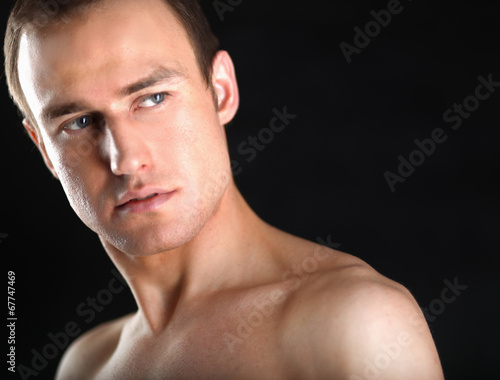 canvas print picture Portrait of a naked muscular man, isolated on black