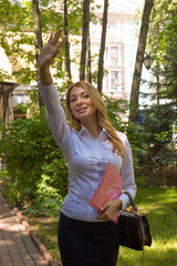 Attractive smiling young businessженщина with a bag wavin