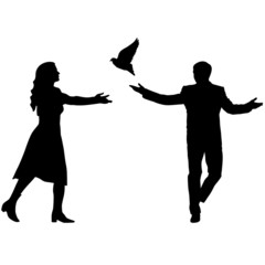 Concept of love or peace. Silhouettes girl and guy released dove
