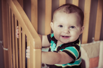 Happy baby standing up in his crib in filtered