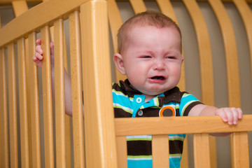 Crying unhappy baby standing in his crib