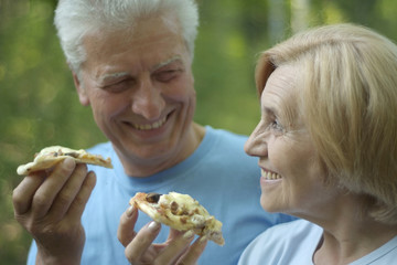 Mature couple eat pizza