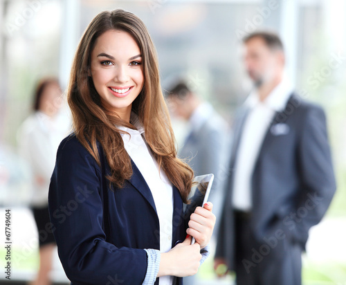 Business woman standing in foreground with a tablet in her hands