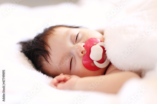Peaceful baby lying on a bed while sleeping in a bright room