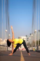 Woman doing stretching yoga exercises outdoors on the bridge