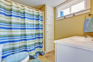 Ivory bathroom interior with stripped blue curtain