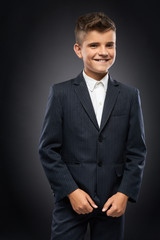 boy in a black suit jacket corrects