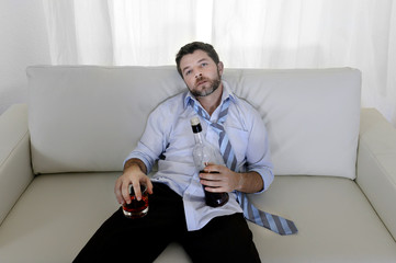 drunk businessman wasted on couch drinking whiskey bottle