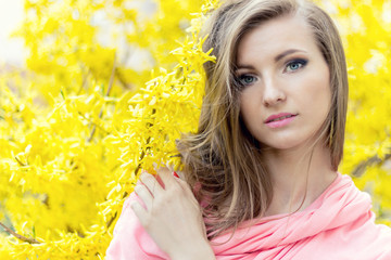 beautiful girl in a pink jacket near shrub with yellow flowers