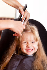 Happy little girl at the hairdresser