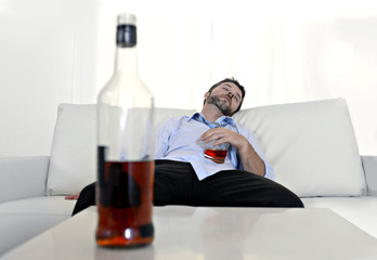 drunk businessman wasted and whiskey bottle in alcoholism