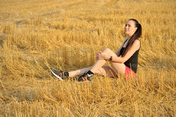 Woman Sitting In Harvested Field