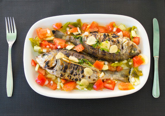 Grilled snappers with tomato salad. Typical mediterranean dish.