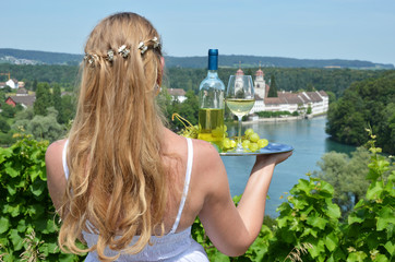 Girl holding wine and grapes against Rhine rive in Rheinau, Swit