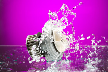 Auto parts, engine cooling pump in spurts of water on purple bac