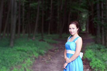 smiling girl stands on a footpath of dark forest