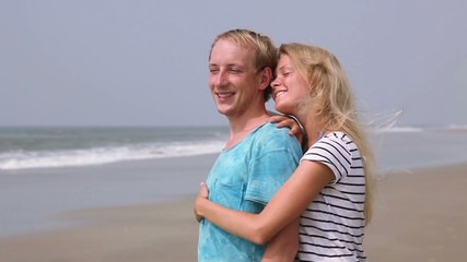 Young and cute couple joy on the beach. Honeymoon near ocean.