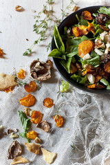 salad with rocket, carrots chips, walnuts and seed in bowl