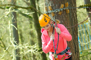 beautiful woman in a special outfit climbing the trees
