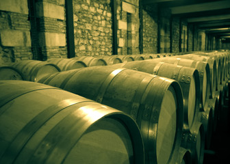 Aged photo of winery with  many wooden barrels