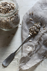 Silver spoon with sunflower seed on wooden white background