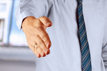 Businessman offering for handshake on office buildings backgroun
