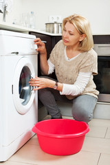 Home laundry. mature woman using washing machine