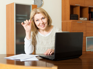 Smiling mature woman fills in the questionnaire in laptop
