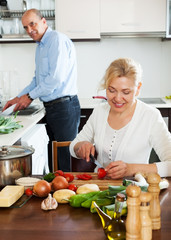 happy mature couple cooking healthy food