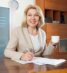 Smiling mature businesswoman with cup of tea