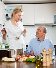 Happy mature woman and elderly senior cooking