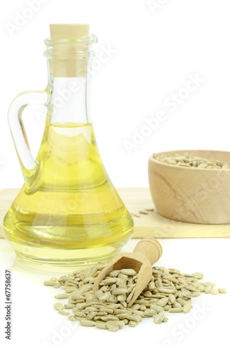 canvas print picture A bottle of sunflower cooking oil and seeds on white background