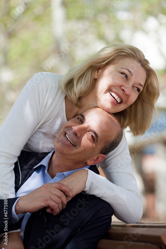 canvas print picture Mature family couple staying outdoor at fall day and smiling