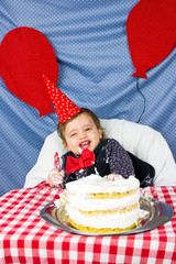 Smiling baby celebrating his first birthday with a smash cake